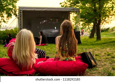 Young woman and girl laying cozy on pillow i green grass and watching film in open cinema in public green park.Back of twofemale in nature enjoying movie on big screen