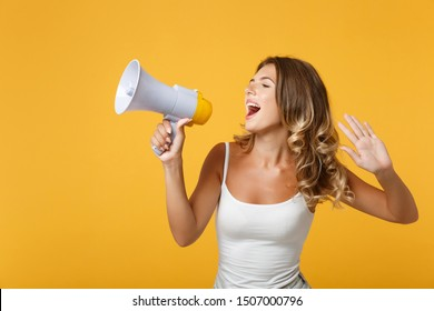 Young woman girl in light casual clothes posing isolated on yellow orange background, studio portrait. People sincere emotions lifestyle concept. Mock up copy space. Scream in megaphone, showing palm