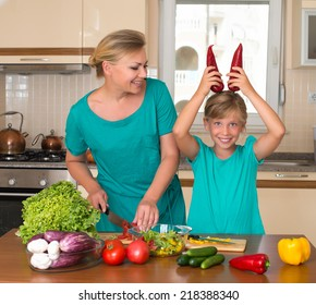 Young woman and girl making fresh vegetable salad. Healthy domestic food concept. Smiling mother and funny playful daughter cooking together, help children to parents.