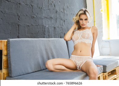 young woman girl model blonde posing at sofa wears white lingerie