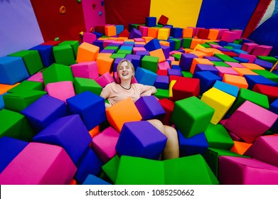 A young woman or girl, mother playing and jumping in soft cubes in the dry pool of the game children's room for birthday. entertainment centre. indoor playground in foam rubber pit in trampoline.