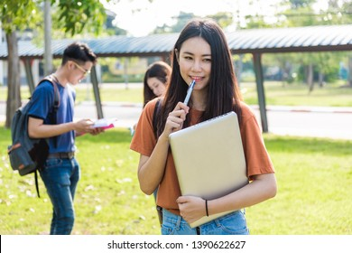 Young woman girl, student hold laptop at college and classmates in background