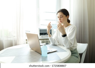 young woman girl student in protective medical mask, hand sanitizer on the table, working with a laptop notebook, online learning education shopping, work at home during quarantine covid-19