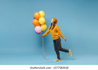 Young woman girl in sweater hat posing isolated on blue background in studio. Birthday holiday party, people emotions concept. Mock up copy space. Celebrating hold colorful air balloons looking aside