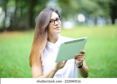 Young woman, girl working with tablet and phone in green field, park with sunshine