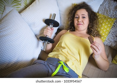 Young woman give up exercise and lying on sofa with chocolate bar and training weight