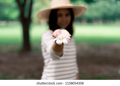 young woman give flower in hand in park in a spring.