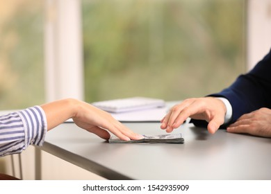 Young woman giving dollar bills to businessman in office, closeup