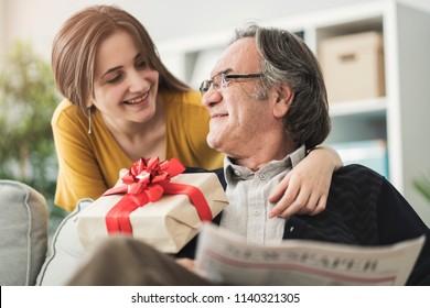 Junge Frau schenkt ihrem Vater etwas