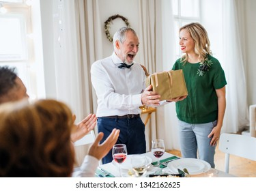 Young woman giving a gift to her grandfather on indoor party.