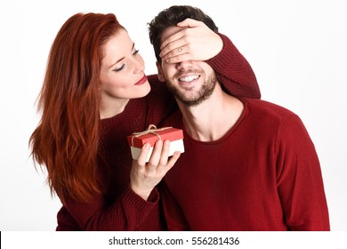 Young woman giving a gift to his man. Beautiful couple dressed in red on white background. Redhead girl