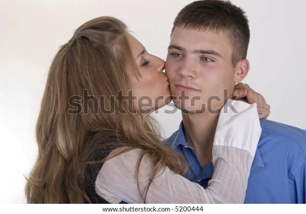 Young woman giving a  young man a kiss on his cheek.