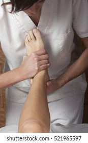 A young woman is giving a massage in a foot
