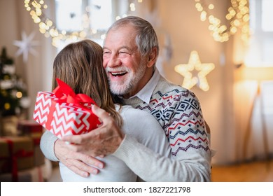 Young woman giving present to happy grandfather indoors at home at Christmas.