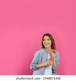 Young woman with glass of chocolate milk on pink background. Space for text