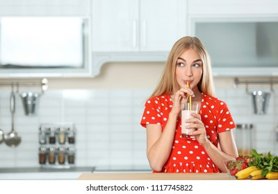 Young woman with glass of delicious milk shake in kitchen