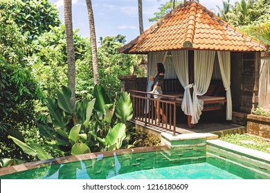 A young woman with a glass of juice in her hands is standing by the private pool against the backdrop of a romantic gazebo and tropical plants. A girl enjoys relaxing at a villa in Bali in Ubud.
