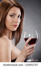 Young woman with glass of red wine.Dark background.