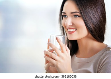 Young woman with a glass of water sitting on sofa in the room