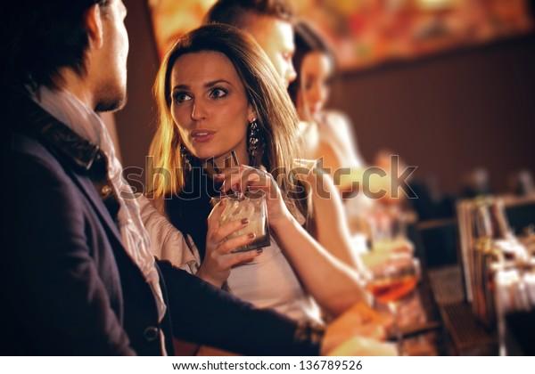 酒を飲みながらバーの男と話をする若い女性