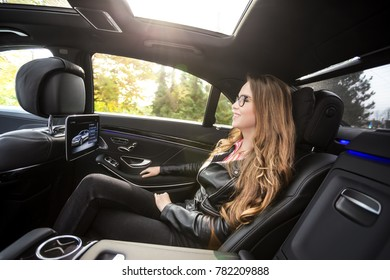 Young woman with glasses and black leather jacket in the luxury car