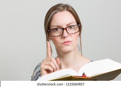 young woman with glasses and a book is pointing with her pointing finger
