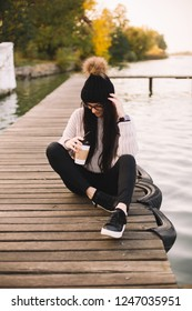 Young woman in glasses with cup of coffee on river pier