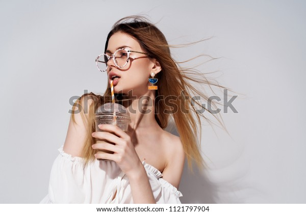 young woman with glasses drinks coffee