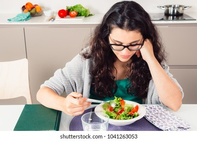 Young woman with glasses eating a boring salad in the kitchen with a book next to her