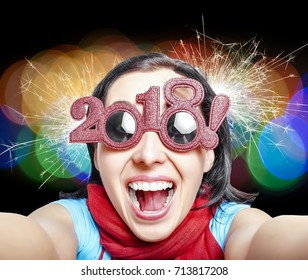 Young woman in glasses in the form of numbers with the inscription 2018 celebrates the New Year. New Year's concept.