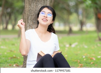 Young woman with glasses has an idea after reading a book.