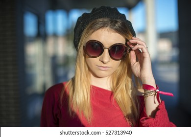 Young woman in glasses and a hat on the street.