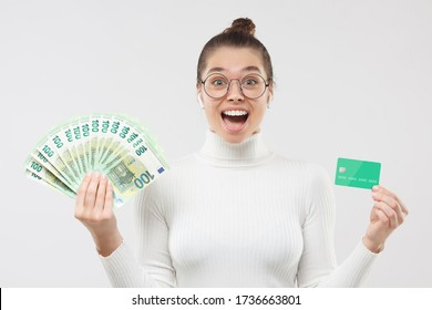 Young woman in glasses, holding fan of hundred 100 euro notes and credit card, feeling excited about big cash, shouting WOW, isolated on gray background. Online payment ads