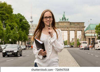 a young woman in glasses holding a pen and a folder and standing on the street in front of Brandenburg Gate in Berlin; thoughts and ideas