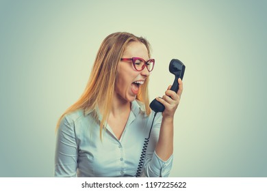Young woman in glasses holding telephone receiver and yelling with anger