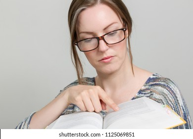 young woman with glasses is pointin at an open book