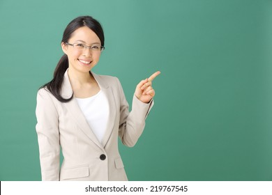 young woman with glasses pointing copy space against blackboard