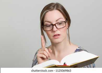 young woman with glasses is reading aloud out of a book