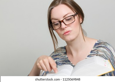 young woman with glasses is reading in a book