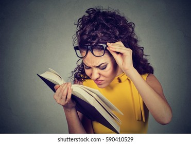 Young woman with glasses reading a book, having difficulties seeing text, has sight problems. Eyesight issues concept. Human face expression