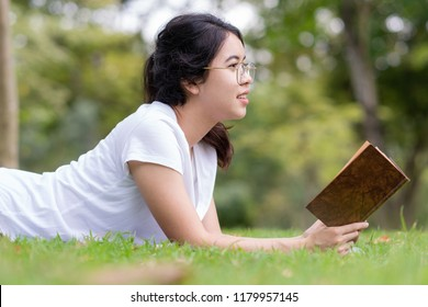 Young woman with glasses reading old book on the lawn.