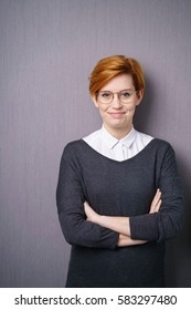 Young woman in glasses with short red hair wearing dark sweater over white blouse standing arms folded against purple wall. Looking at camera, vertical portrait with copy space