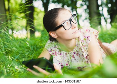 young woman in glasses uses a digital tablet on the nature
