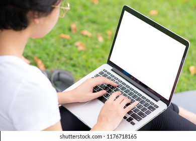 Young woman with glasses  using laptop on the lawn.