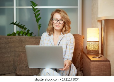 A young woman in glasses works remotely on a laptop in her apartment. A lady during a video business briefing at home. A pretty female student listening to an online lecture.