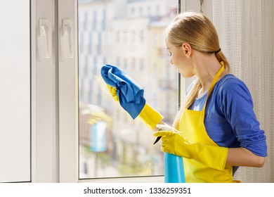 Young woman in gloves and apron washing window pane at home with rag and spray detergent. Blue yellow color. Cleaning concept.