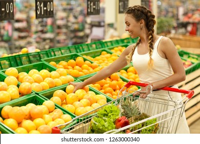 Young woman go shopping in supermarket. Female customer choosing citrucses in fruit section. She taking oranges and grapefruits from basket. Buyer holding hand on trolley.