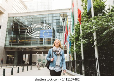 Young woman goes near the Parliament building of European Union in Brussel city.