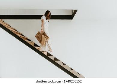 Junge Frau ging die Treppe hinunter in einem modernen Haus mit Kleider.