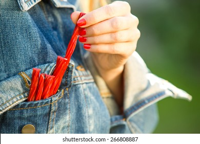 Young woman going to eat licorice candy. focus on fingers